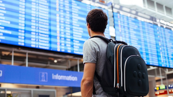 A man with a rucksack on his shoulders is looking at the departure board at an airport
