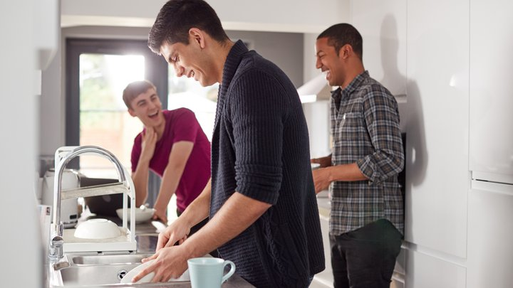 Three guys are sharing a joke in a kitchen while one of them is doing the dishes