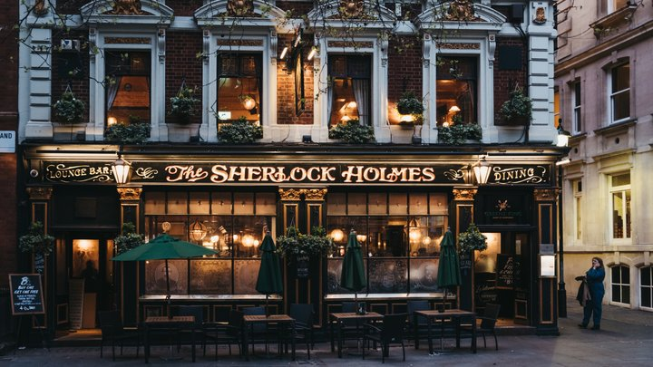 """An invitingly lit up traditional English pub from the outside. The pub sign says """"Sherlock Holmes""""."""