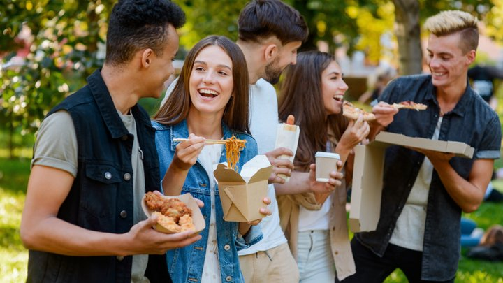 A group of students are stood around eating takeaway meals and chatting outdoors in a park.