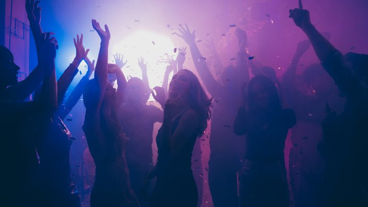 A joyful crowd at a nightclub raise their hands up as a shower of confetti rains down from the ceiling.