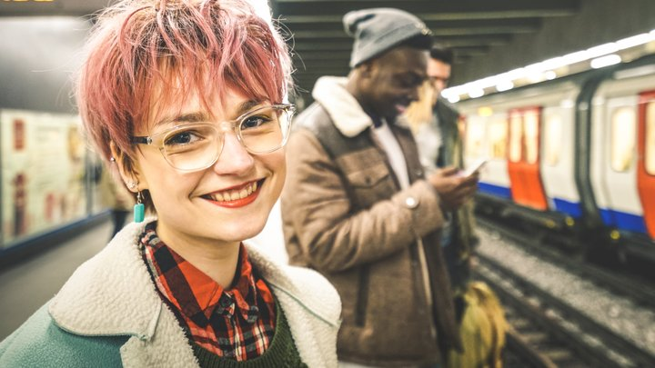 A group of friends are waiting for an underground train. A young woman in the foreground smiles at the camera.