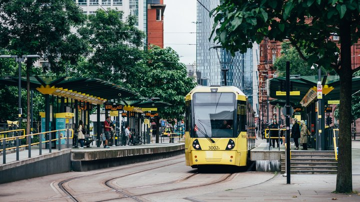 Passengers are boarding a yellow tram at a busy city tram stop