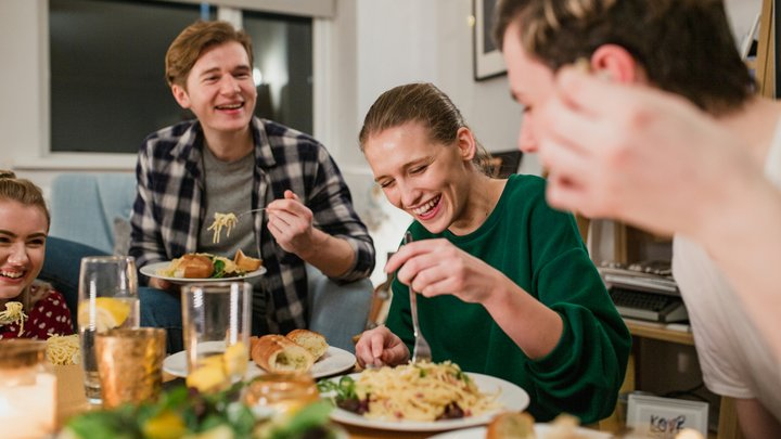 A group of friends are sharing a meal at a dining table with big smiles on their faces.