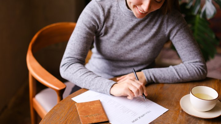 A woman, sat at a table in a cafe, is filling out an application