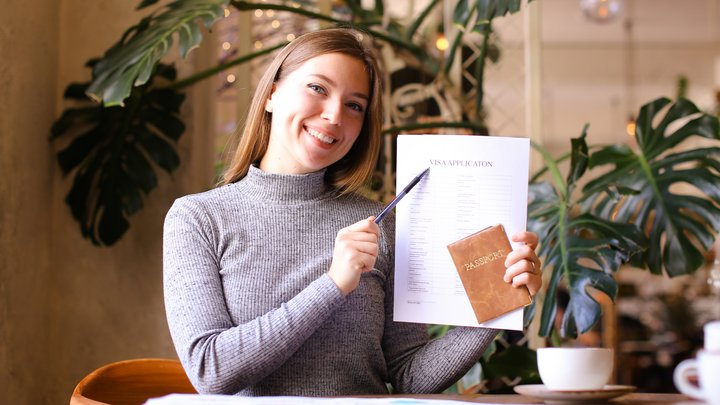 A smiling woman is holding up a visa application and a passport